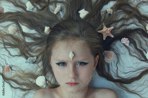 Young mermaid with seashells Poster