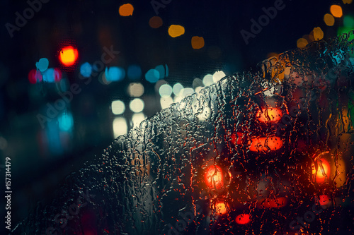 blurry cars and lights in traffic in a rainy night seen through windscreen Poster