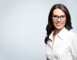 young smiling brunette businesswoman in glasses, with copyspace