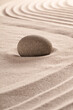 Purity concept by round stone on raked sand in zen meditation garden.