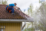 Caucasian man is washing the roof with a high pressure washer. He is wearing safety harness on a slippery roof. - 157327891