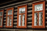 Ancient house of logs of the twentieth century in Russia, Russian wooden house with orange window frames