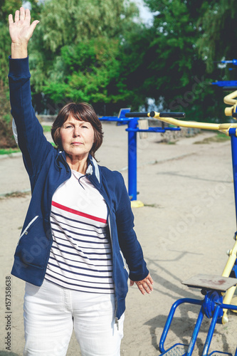 Cute retired woman performs gymnastic exercises on street