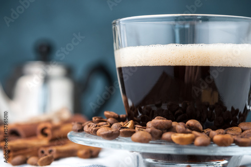 Glass Cup of hot coffee with foam close-up scattered grain.