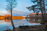 Tranquil landscape. Sunset on the lake. Wooden bench on the shore