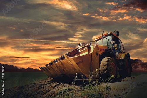 Foto op Canvas Zee zonsondergang Yellow tractor on sky background