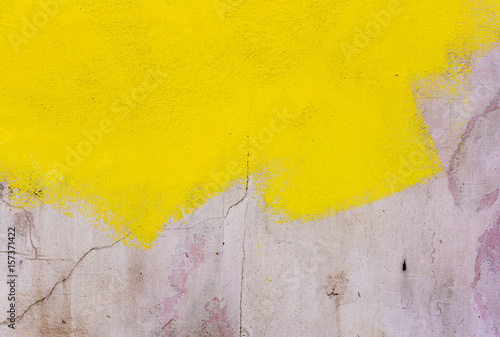 Yellow paint on the concrete gray wall