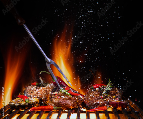 Beef steaks on the grill with flames - 157379803