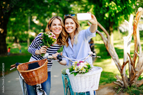Two young women exploring the city on bicycles and doing selfie Poster