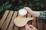 Closeup woman hand holding cup of coffee in cafe