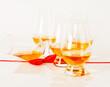 Set of single malt tasting glasses, single malt whisky in a glasses, white background, red bow