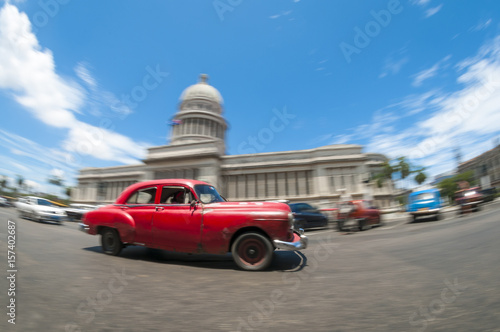 Deurstickers Havana Brightly colored classic American cars serving as taxis pass on the main street in front of the Capitolio building in Central Havana, Cuba