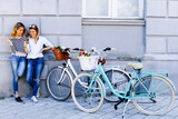 Two young women with bikes using smartphone - 157409618