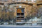 Старое разбитое окно заколоченное досками на кирпичной стене