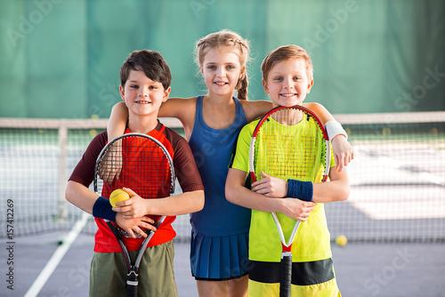 Fotobehang Tennis Cheerful kids having fun on tennis court