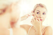 woman squeezing pimple at bathroom mirror