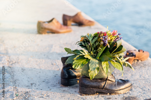 Poster Shoes on Danube with bunch of flowers