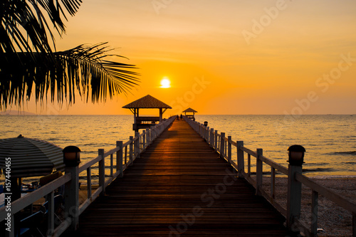 The wooden bridge on sea at sunset, Thailand.