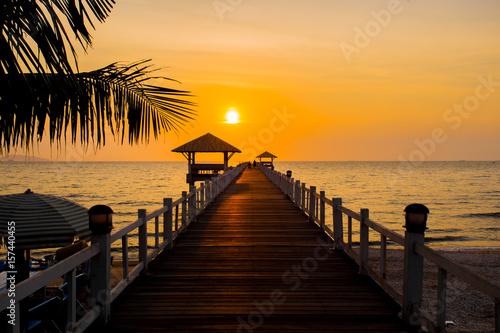 Plexiglas Pier The wooden bridge on sea at sunset, Thailand.