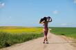 девушка прогуливается по дороге вдоль полей