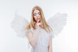 Angel keeps the secret. Young, wonderful blonde girl in the image of an angel with white wings.