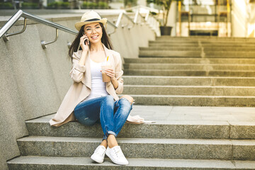 Beautiful young Business Woman using phone. Slow Motion. Beautiful woman in jeans enjoying sunny morning in the city and drinking coffee. Lens Flare.