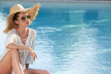 Beautiful young woman sitting by swimming-pool - 157516081