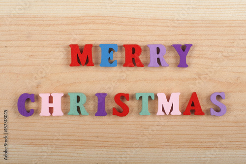 Poster MERRY CHRISTMAS word on wooden background composed from colorful abc alphabet block wooden letters, copy space for ad text