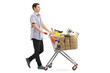 Young man pushing a shopping cart filled with groceries