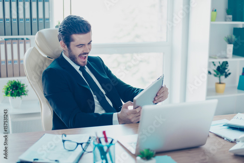 Cheerful young businessman is plying a game on his tablet in office Poster