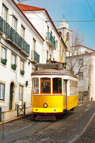 Poster Famous vintage yellow 28 tram on street of Alfama, the oldest district of the Ol