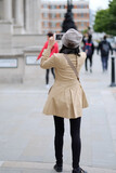 A woman takes pictures of the sights of the city. London, Great Britain.