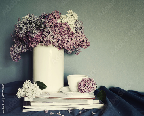 Bouquet of lilac flowers in a white vase, a cup of tea and a pile of magazines, a decor in vintage style. Spring romantic bouquet for your holiday. Still life with spring flowers