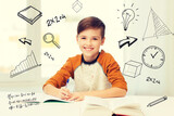 Fototapeta smiling student boy writing to notebook at home