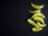 Fresh light green and yellow chili peppers isolated on black background