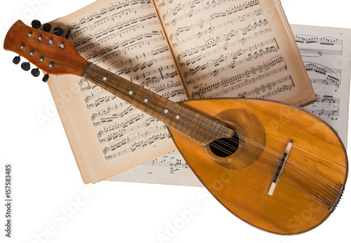 Vintage mandolin on a background of open sheet music book. - 157583485
