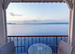 Cafe bar terrace, view at Mediterranean sea. Evening scenery, Ormos Navarinou harbor, Pilos town, Greece.
