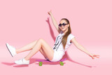 Pretty young casual dressed woman in sunglasses sitting on skateboard.