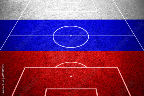 Empty soccer field with ground lines on sunny grass texture with painted Russia flag background. Goal side perspective used.