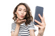 woman blowing kiss while taking selfie on smartphone isolated on white