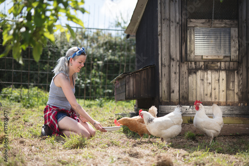Poster Young woman feeding Chickens