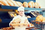 Baker man is showing tasty bread