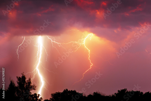 Fork lightning over dark orange sky on stormy day Poster