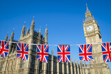 Union Jack bunting flying in front of the Houses of Parliament at Westminster Palace with Big Ben under bright blue sky in London, England