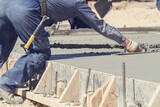 Construction worker leveling concrete pavement outdoors. - 157762408