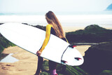 Professional female surfer walking to the ocean waves holding her surfboard, female surfer holding copy-space surfboard
