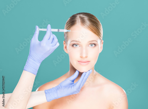 Young and beautiful woman having skin injections over teal background Poster