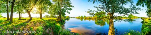 Foto Murales Sommerliche Landschaft mit Wiesen, Bäumen, Sonne und Fluss