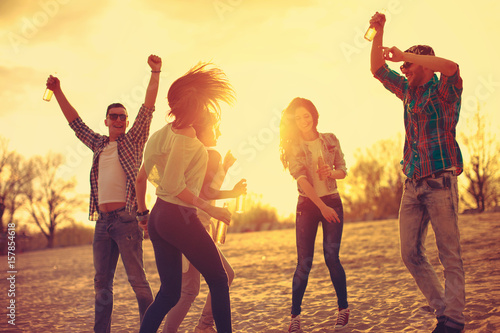 Happy young people having fun on the beach and drinking beer - 157854618