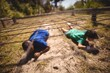 Kids crawling under the net during obstacle course